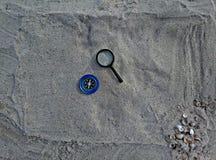 Kompass und Vergrößerungsglas auf Sand stockfoto