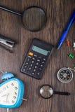 Kompass, Wecker, Vergrößerungsglas und Taschenrechner Stockfotografie
