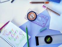 Kompass, Werkzeuge, Notizblock mit einem Glückwunsch zum Vater, Farbe zeichnet an Stockbilder