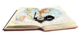 Kompasset ligger på terrängöversikten, kartbokbok Royaltyfri Fotografi