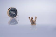 Kompasset och den guld- färgkronan modellerar med pärlor Royaltyfri Foto