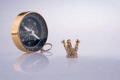 Kompasset och den guld- färgkronan modellerar med pärlor Arkivbild