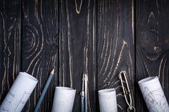 Kompassse, Rollen von der Zeichnung und ein Bleistift auf einem dunklen hölzernen Hintergrund stockbilder