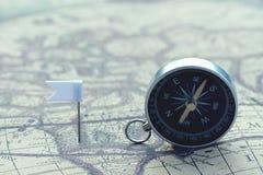 Kompasu i flagi szpilki na plama rocznika światowej mapie, podróży pojęcie zdjęcia royalty free