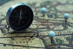 Kompasu i flagi szpilki na plama rocznika światowej mapie, podróży pojęcie zdjęcia stock