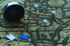Kompasu i flagi szpilki na plama rocznika światowej mapie, podróży pojęcie obrazy stock