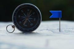 Kompasu i flagi szpilki na plama rocznika światowej mapie, podróży pojęcie fotografia stock