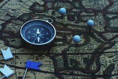 Kompasu i flagi szpilki na plama rocznika światowej mapie, podróży pojęcie obraz royalty free