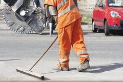 Kompetent arbetare i vägkonstruktionsplats med den orange likformign Royaltyfri Bild