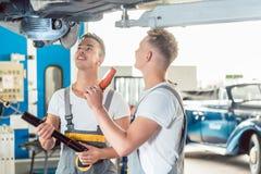 Kompetent auto mekaniker som byter ut st?td?mparna av en bil royaltyfri foto