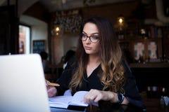 Kompetent blogger för kvinna som har webinar via netbook royaltyfri bild