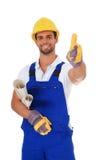 Kompetent byggnadsarbetare som visar upp tum Arkivfoto