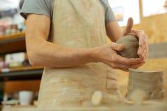 Kompetent f?rlage med starka h?nder som rullar lera in i h?ger boll fotografering för bildbyråer