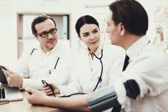 Kompetent kardiologmåtttryck av den vuxna mannen med tonometer ge ? första erfarenh ? digitalt högt isolerat tryck för makrobilds royaltyfri fotografi