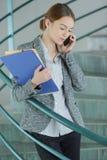 Kompetent kvinnlig arbetare som använder celltelefonen royaltyfria bilder