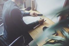 Kompetent märkes- caucasian manteckningsabstrakt begrepp skissar med pennan Process för konstarbete Idérik hobby Notera idéer i k Arkivbild