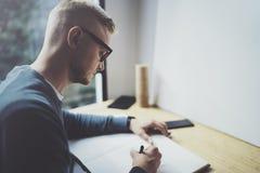 Kompetent märkes- caucasian manteckningsabstrakt begrepp skissar med pennan Process för konstarbete Idérik hobby Notera idéer i k Arkivfoto