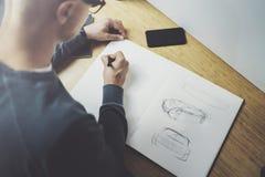 Kompetent märkes- caucasian manteckningsabstrakt begrepp skissar med pennan Process för konstarbete Idérik hobby Notera idéer i k Royaltyfria Foton