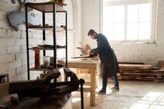 Kompetent självständig snickare som arbetar med trä i snickeri w Arkivbild