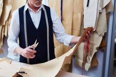 Kompetent skräddare Cutting Clothing Patterns royaltyfri foto