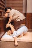 Kompetent trevlig asiatisk massös som gör thailändsk massage royaltyfria foton