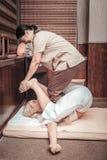 Kompetent trevlig asiatisk massös som gör thailändsk massage arkivbilder
