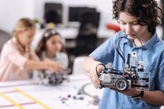Kompetent ung elev som visar roboten på skolan Arkivbild