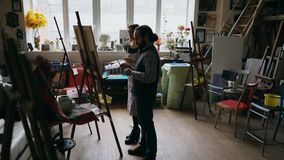 Kompetent ung flicka för konstnärmanundervisning som drar målningar och förklaring av grunderna i konst-grupp Fotografering för Bildbyråer