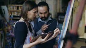 Kompetent ung flicka för konstnärmanundervisning som drar målningar och förklaring av grunderna i konststudio Arkivfoto
