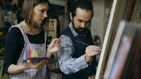 Kompetent ung flicka för konstnärmanundervisning som drar målningar och förklaring av grunderna i konststudio Royaltyfri Bild