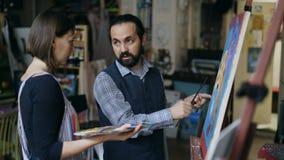 Kompetent ung flicka för konstnärmanundervisning som drar målningar och förklaring av grunderna av ljus i konststudio Royaltyfria Bilder