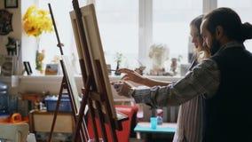 Kompetent ung flicka för konstnärmanundervisning till att dra målningar och förklaring av grunderna i konststudio Arkivbilder