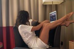 Kompetent ung kvinna i den moderna lyxiga lägenheten, sitta som är bekvämt i fåtöljinnehavdator på hennes varvar som kopplar av arkivfoton