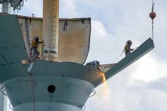 Kompetenta welders tar ifrån varandra avsnitt av ett gammalt vattentorn Royaltyfria Foton