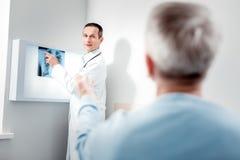 Kompetenter Arzt, der Röntgenstrahlbild demonstriert lizenzfreies stockfoto
