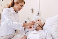Kompetenter freundlicher Doktor, der mit ihrem älteren Patienten spricht Stockbild