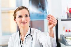 Kompetentna lekarka analizuje promieniowanie rentgenowskie wizerunek Obrazy Royalty Free