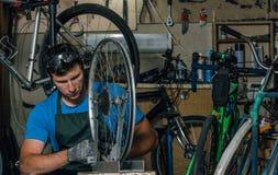 Kompetentny rowerowy mechanik w warsztacie naprawia rower zdjęcie stock