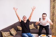 Kompisar som håller ögonen på fotbollsmatchen på tv med seger, skriker hemma Royaltyfri Foto