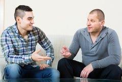 Kompisar som pratar i hemmiljö Royaltyfria Bilder