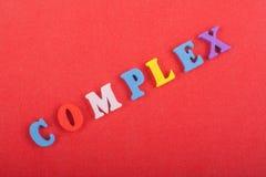 KOMPLEXT ord på röd bakgrund som komponeras från träbokstäver för färgrikt abc-alfabetkvarter, kopieringsutrymme för annonstext Arkivbilder