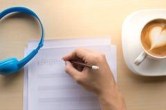 komponować muzyka nutowego odgórnego widok z ręki writing błękitem i kawą Zdjęcie Royalty Free
