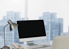 Komputer na biurku przeciw miasta okno Zdjęcie Royalty Free