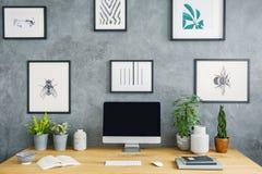 Komputer stacjonarny na drewnianym biurku z roślinami w popielatym workspace wewnątrz fotografia royalty free