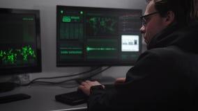 Komputer w nowożytnej bibliotece Na komputerach i desktop klawiaturze Hacker próby łamać w krytyczną informację Mężczyzna w zmrok zdjęcie wideo