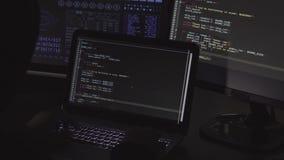 Komputerowego hackera writing kod używać komputery i laptop w ciemnym pokoju zbiory