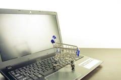Komputerowego notatnika pusty ekran z wózek na zakupy na drewno stole zdjęcia royalty free