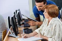 Komputerowy adiunkta mienia schowek Podczas gdy Starsza kobiety Writing notatka Zdjęcia Royalty Free