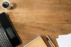 Komputerowy laptop, filiżanka, notatnik i pióra na rocznika grunge drewnianym biurku, Obraz Royalty Free