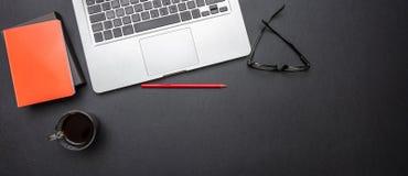 Komputerowy laptop i telefon komórkowy na czarnego koloru biurowym biurku, sztandar fotografia royalty free